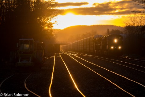 CSX Q293 rolls west against a backdrop of the rising sun at Palmer, Massachusetts on November 18, 2015. The Tenneyville Bridge is visible in the distance. My set up time: about 15 seconds.