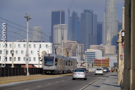 Here's the same light rail train exposed from the same vantage point, but using a telephoto focal length, which compresses the distance and allows for the skyscrapers to visually loom above the road.
