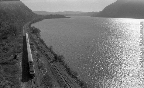 A Metro-North train for Poughkeepsie approaches the tunnels at Breakneck Ridge, New York. To the right are the glinting waters of the Hudson River.