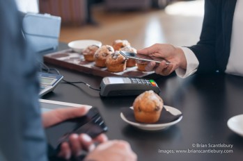 Making contactless payment in cafe with mobile phone a growing trend with mobile phone held close to card reader