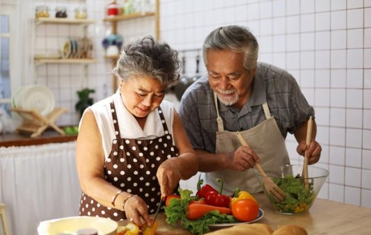 Image: senior-couple making food in kitchen