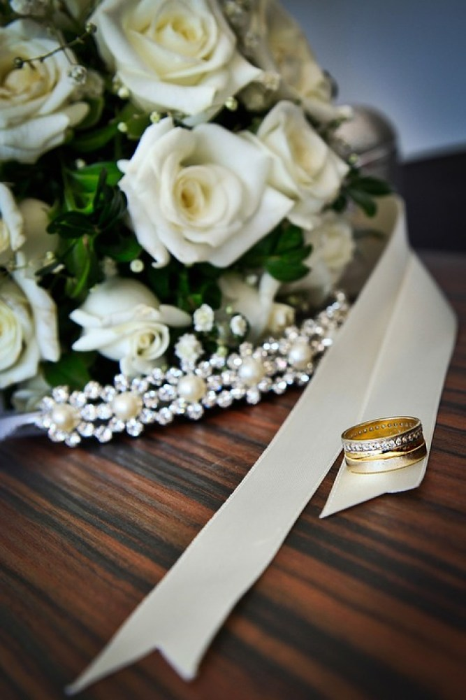 white roses with wedding rings