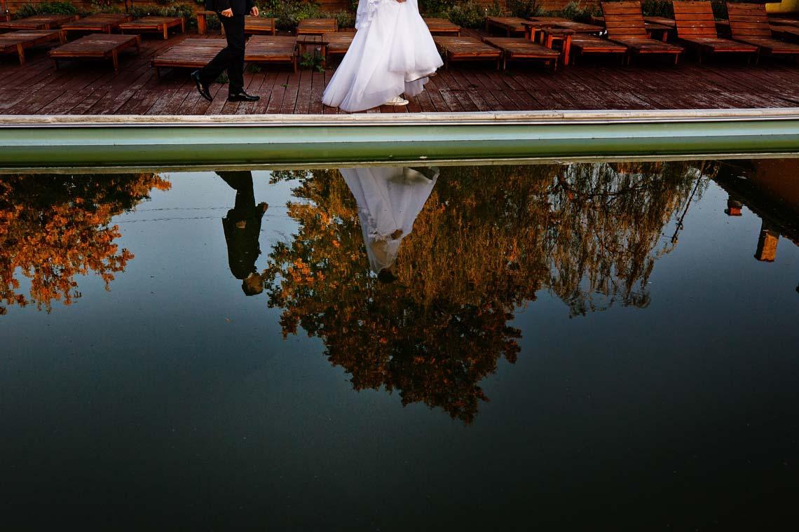 Efteraarsbryllup brudepar spejler sig i vandet Bridenista