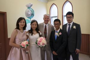 Officiant Re. Ray Cross pauses for a picture with a wedding party after their wedding
