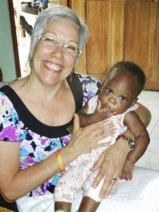 Volunteer holding a baby girl.