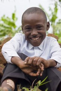 Smiling boy sitting on the grass.