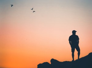 man stands on the mountains at sunset illustrating staying single after a breakup. Therapist kim moustoukkis provides counseling in bloomington, IL for life transitions such as breakups