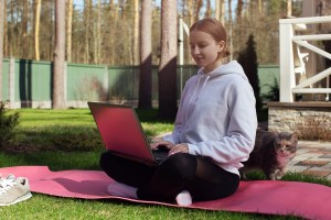 young woman sits on a yoga mat outside during online therapy in illinois for anxiety, depression, and grief and loss