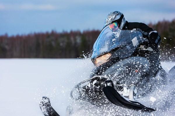 In deep powder snowdrift snowmobile rider driving fast.