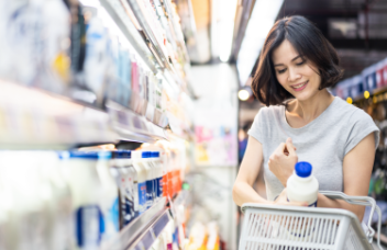 woman grocery shopping, she smiles as she places a carton of milk in her basket