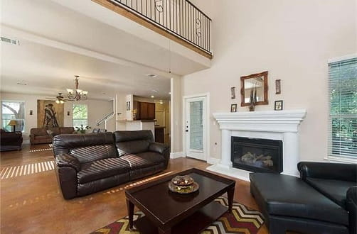 Inside view of Austin Sober Living home with elegant room in two story house with hardwoods, fireplace, and leather couches.