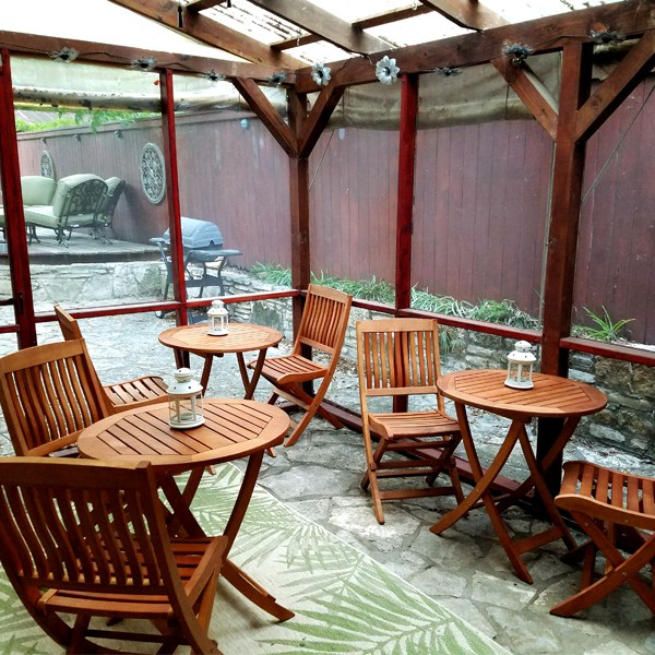 Picture of enclosed patio with teak wood furniture and barbeque pit outside