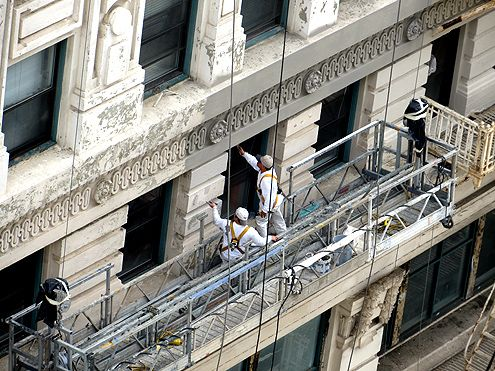 Gray paint being applied to the facade