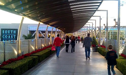"In 2000, a 600-foot ""Bridge of Gardens"" was completed by South Coast Plaza in Orange County, CA (designed by Kathryn Gustafson) that successfully tied together the main shopping center with their struggling west wing because the new bridge and it's visually appealing design encouraged shoppers (read: pedestrians) to walk across without complaint"