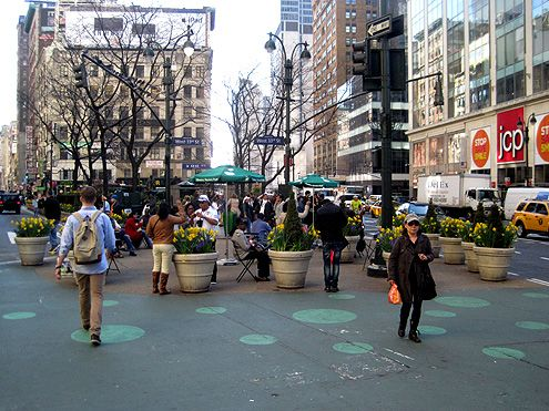Using planters and paint on the ground are just some of the inexpensive ways of expanding public space on what was once an asphalt street