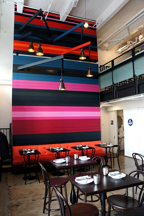 A beautiful colorful banded mural is the centerpiece of the restaurant space