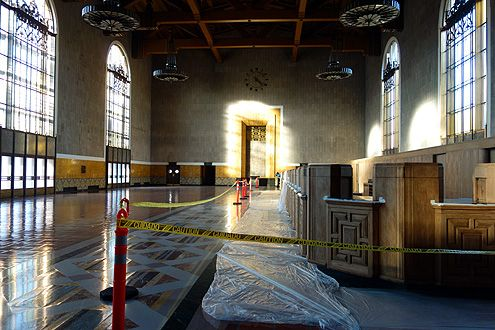 A peek behind the curtain reveals the beautiful grand ticket hall where the original ticket booths are being restored