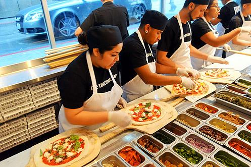 An assembly line of custom made to order pizzas