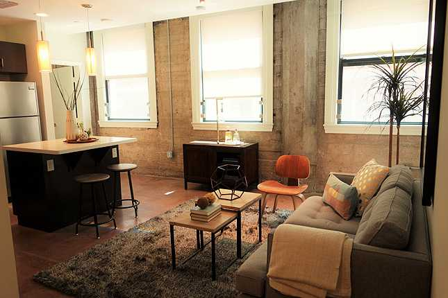 A one bedroom model unit at The Mint shows lots of windows and beautiful concrete floors and columns