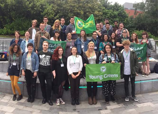 A large group of Young Greens holding official Young Greens, Federation of Young European Greens, and Climate Sense flags.
