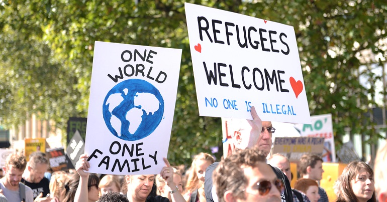"A protest with two signs, one reading ""one world, one family"" and the other reading ""Refugees welcome, no one is illegal"