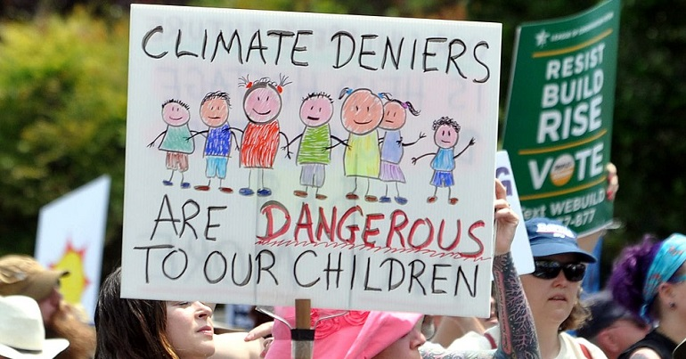 "Climate change protest placard reads: ""Climate deniers are dangerous to our children"""