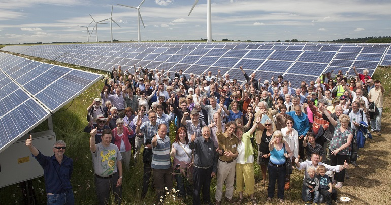 Crowd of people in front of wind turbines and solar panels
