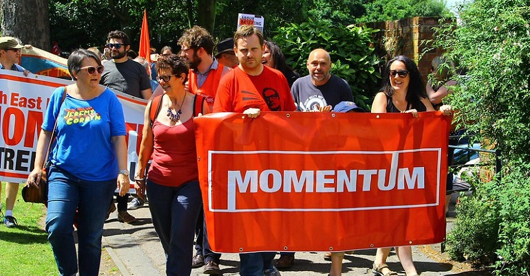 Campaigners marching behind a Momentum banner