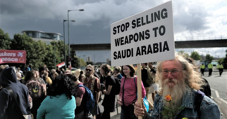 """A photo of campaigners at a protest against the arms trade. One is holding a sign reading """"stop selling weapons to Saudi Arabia"""""""