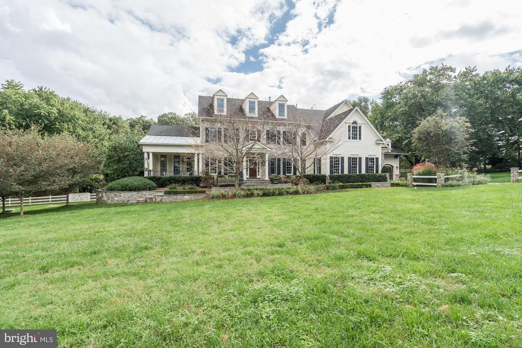 A rare opportunity in Great Falls, close to Reston, Herndon, and the tech corridor. A large, beautiful, stone country colonial with a lot of character, fenced in on 2 acres. This is a true entertainer~s gem. With all the details and extras this house could not be replicated for the asking price.You enter the house to a two story, marbled floor foyer with a chandelier. It opens to the living room and formal dining room. The entire house, including parts of the outdoor areas is wired for sound. Off the living room is a large sunroom that lets out onto the slate front porch. This room comes with a wet bar and a fireplace, so it is a great place for entertaining. The sunroom also lets onto a screened porch with a slate patio, a vaulted, beamed bead board ceiling and a wood burning fireplace. This porch can be accessed by the library that has cherry built-in cabinets on two walls and bay windows overlooking the back yard. These areas are accessed by a corridor with the guest powder room.The foyer also gives onto the rear of the house, into a family room with coffered ceiling, recessed lighting and a stone, wood burning fireplace. Next to this space is a breakfast area with French doors leading to a veranda large enough for dining and ample room for a grill. The kitchen has two tone, inset cabinets with a rub finish. It has a huge butcherblock island with a prep sink and warming drawers. There are two additional sinks, two ovens, two subzero refrigerators, a wolf range with water, a convection oven and a microwave all built in. There is a generous walk-in pantry with a third subzero. Next to the kitchen is an extra space with a small eating nook, a built-in credenza, a double desk homework area and additional cabinets. The butler pantry has a hammered copper sink and a wine fridge. A large mudroom with the family powder room accesses the single car garage, the oversize two-car garage and an open breezeway, wired for sound, that can be used for rainy-day outdoor entertainm