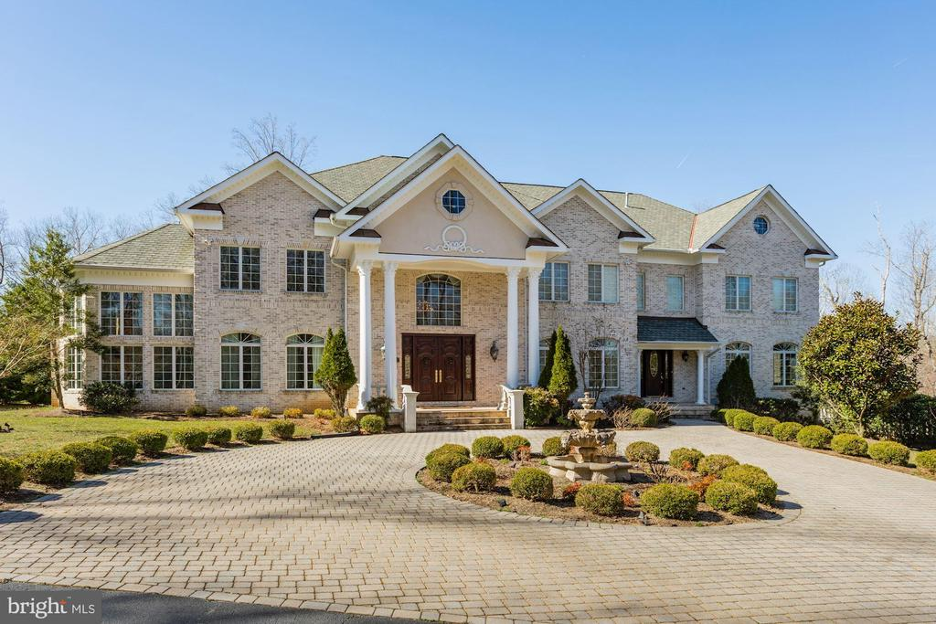 This exquisite gated estate on 2.6 acres sits atop of a knoll and looks out over the pool to a west forest. This all brick home was custom build for the owner with a 4 car garage, circular driveway with a fountain feature. As you arrive at the front, the quality is evident from the carved lion heads on the doors or the sweeping staircases with hand forged stair railings. The large estate has a crystal chandelier over the marble foyer as you walk between the stairways, you enter into the great room with soaring ceilings and floor to wall windows you will love. The fireplace and the wide plank cherry floors as well as the coffered ceiling gives this room an elegant feeling. Off the formal living room you will find a side conservatory; also with a fireplace and 18ft ceiling with windows on both sides. The library is to the rear and the kitchen as well. The kitchen has porcelain floors, a huge breakfast room, and cherry cabinets offer thermador professional appliances like a 60~ range with double ovens and a high CFM exhaust, warming drawer, microwave and 48~ refrigerator. Off the kitchen is a smaller family room with a fireplace and grand views and full catering kitchen.As you ascend to the upper level, you will find the beautiful hardwood floors here as well. You get a closer look at the detailed molding. On this level are 5 very large bedrooms all with suite baths, hardwood floors, and walk in closets. The master boasts a three sided fireplace, sitting area, and a grand master bath with 2 person Jacuzzi tub and shower with body sprayers and closets with built in shoe closets, center island and window seat.The lower level is exquisite with porcelain flooring, billiards, movie theater with stage seating and exercise room as well as a wine cellar and bedroom with full bath; fireplace, full bar and caf~ which walks out to the pool.
