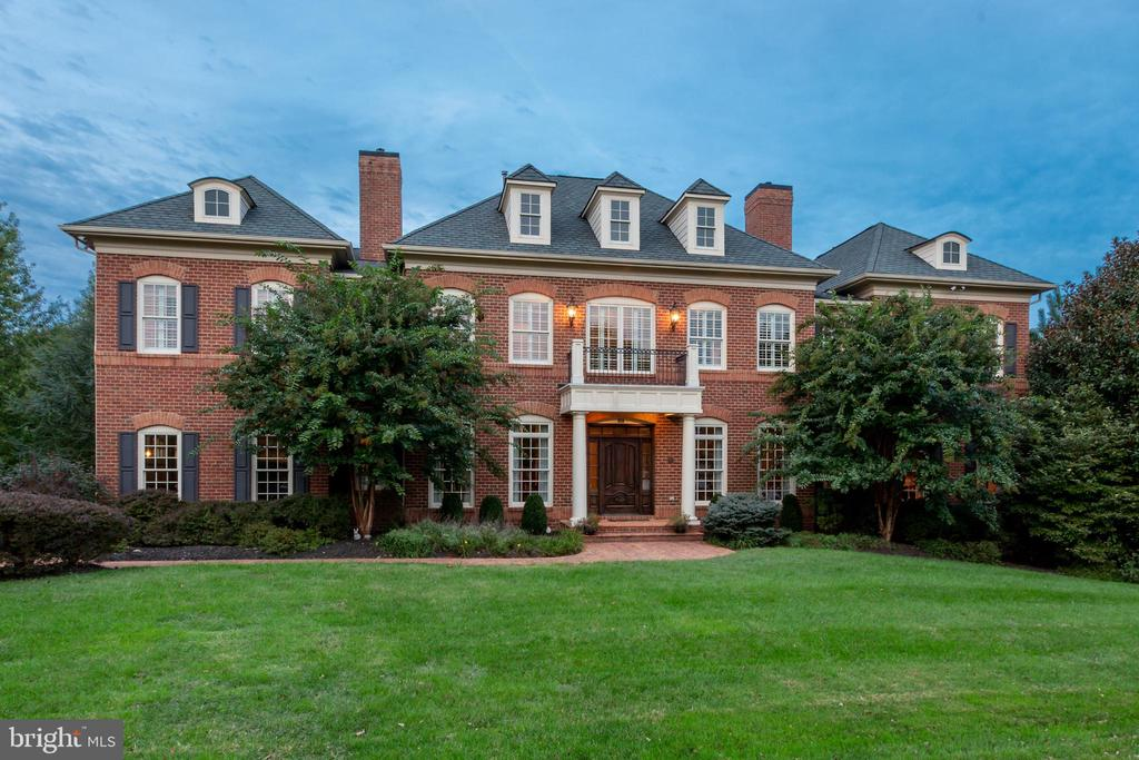 Minutes from Tyson's Corner, Metro, Wolf Trap, and Dulles Airport, on two acres with plenty of privacy, sits this upgraded, custom all-brick colonial. Keen attention to detail throughout 10,000 square feet make this home a luxurious sanctuary in one of the fastest-growing metropolises in the country. Ten foot ceilings and 15-inch crown moldings create an impressive main level, with arched doorways and floor-to-ceiling windows that bathe sanded-in-place wood floors in plenty of natural light. You~ll stay cozy at night with fireplaces in three rooms. Chefs, bakers and entertainers delight in the kitchen, which has 3 Wolf ovens, a 6-burner Wolf stove with hood, 3 dishwashers and 2 sinks. Keep your parties going outside via French doors leading to balconies and screened porch off the main level, as well as a whole-house indoor-outdoor sound system. Upstairs are five out of seven spacious bedrooms, including the master suite, which boasts soaking tub and dual entry shower for the master bath. You~ll appreciate the view from a specially-designed slate balcony for the master suite, which overlooks professionally-landscaped grounds adorned with your personal peaceful forest: an array of tasteful plantings and more than 70 trees. In the lower level, keep what really matters in a stunning 5,000 bottle capacity wine cellar, and enjoy your keep at the large bar, alongside gym, recreation room, powder room, huge bedroom with full bath, and plenty of storage. Enjoy outdoor access from all lower level rooms with French doors in each room, which will take you to a spacious patio with an oversized fireplace, koi pond, and waterfall. Follow the stone walkway to the three car garage, as well as a handicap-accessible guest suite with private entrance. The security system keeps you and loved ones protected with cameras over the entire property, as well as a whole house backup generator. Extravagance awaits you on Dara Lane.