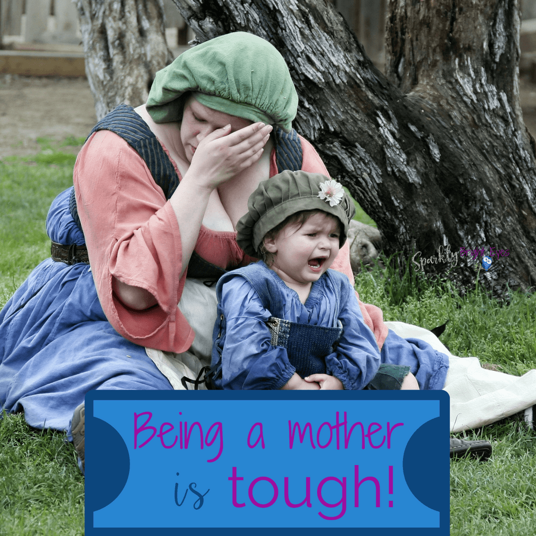 Being a mother is tough Upset mother holding distraught toddler in her lap