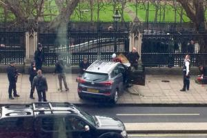 Police gather outside the Houses of Parliament after a shooting. An officer was stabbed