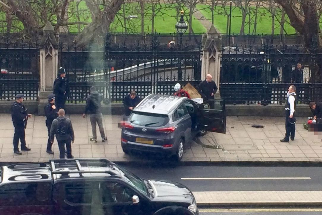 Police gather outside the Houses of Parliament after a shooting. An officer was also stabbed