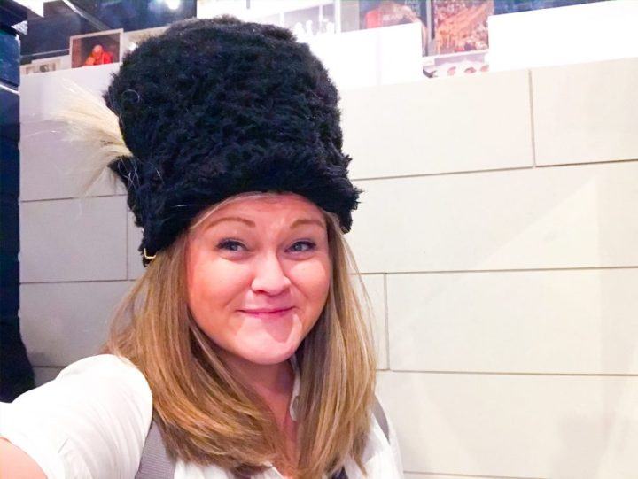 A picture of Bex wearing a tall black furry Guardsman hat like the ones at Buckingham Palace