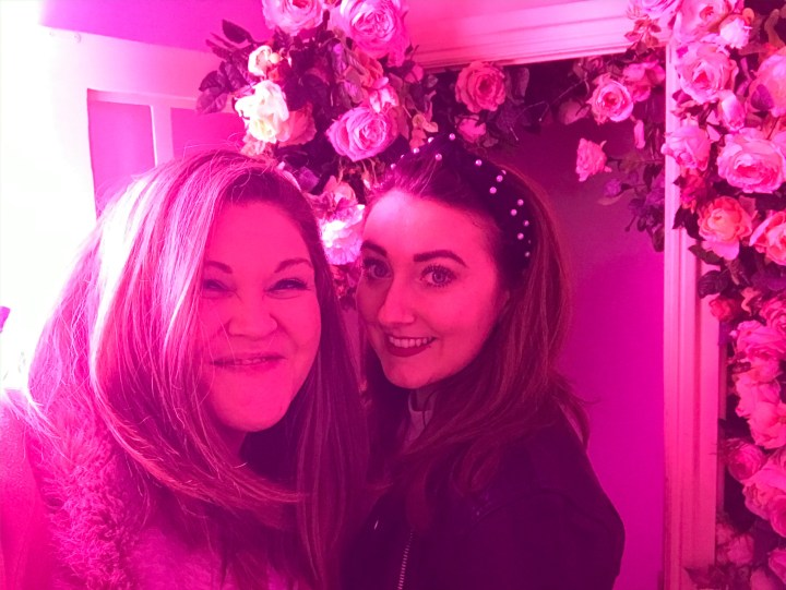 Bex and her friend post in front of the bright neon lights and flower wall