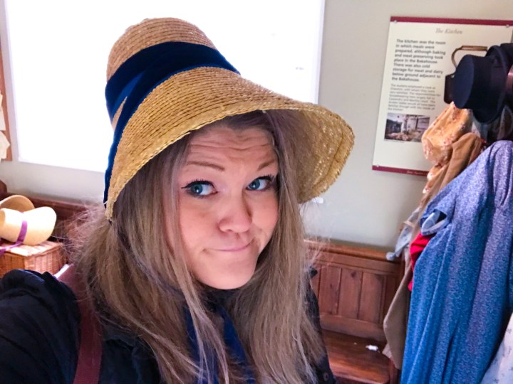 Bex wearing a Jane Austen Bonnet with a bemused look on her face