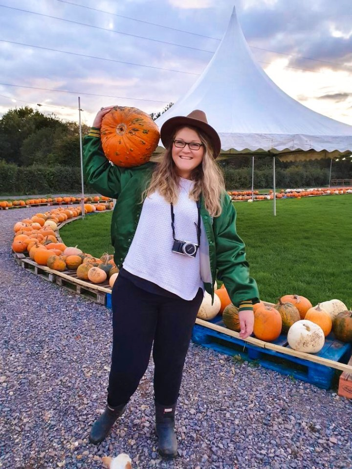 Bex carrying a very big pumpkin on her shoulder with one arm. She is smiling and facing the camera wearing a fedora hat, bomber jacket and wellington boots. The 2020 pumpkin display at Sunnyfields Farm in Southampton, Hampshire.
