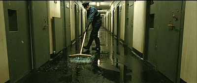 Hunger. A prison guard sweeps piss dispersed by the H-block prisoners.