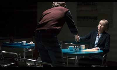 Director Katherine Hudson (uncredited*), CEO of multinational Brady Corp., gets her news at a tiny plastic table in a cafeteria with dirty dishes.""