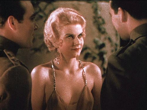 A cobra mesmerizing its prey: Helen (Jean Harlow, center) fixes her gaze on Monte (Ben Lyon, right) as brother Roy (James Hall, left) introduces them. This scene, shot in two-strip Technicolor, is the only Hollywood film to record in color Harlow's flaxen blond hair and blue eyes.