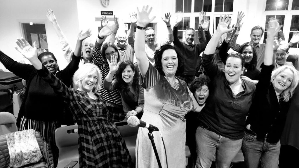 A black and white photo of Bright Soul Choir members. They are all waving, smiling and laughing.