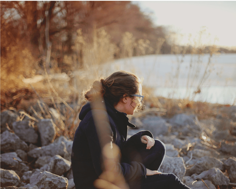 A photo of a white young woman,  wearing blue glasses, with light brown hair pulled back into a low bun. She is sitting on some rocks near some water and looking out into the distance. There is lots of late afternoon sunlight surrounding her and she looks deep in thought.