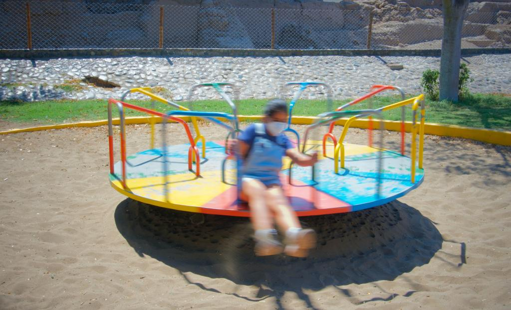 The image is of a person, wearing a mask, sitting on a spinning roundabout.