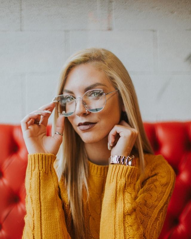 frau-mit-blaulichtfilter-brille-auf-roter-couch