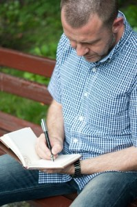 man_writing_journal_bench