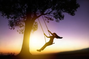 woman on a swing at sunset
