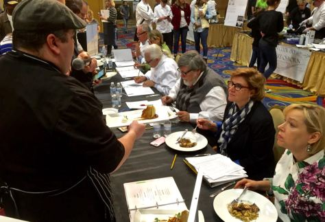 A cooking team chef presents a dish to the food judging panel at the 2016 Cast Iron Cook-Off in Charleston WV.