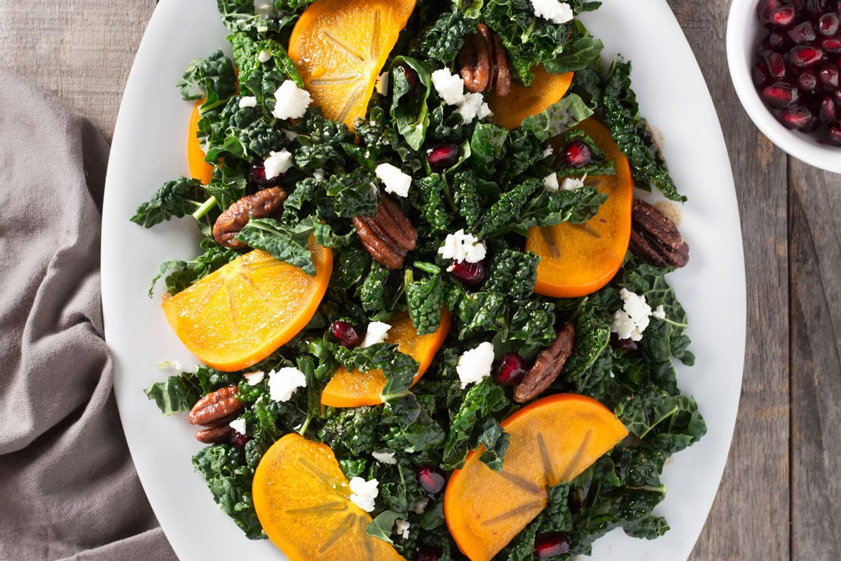 Close up overhead shot of a platter of kale salad with pomegranates, persimmons, maple butter pecans and feta cheese.